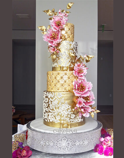 gold custom wedding cake with pink flowers