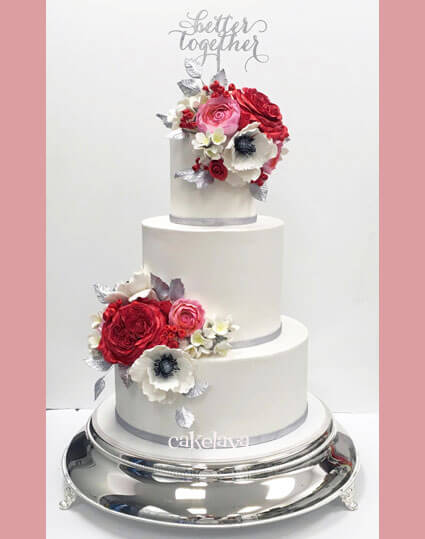 white wedding cake with pink and red handcrafted flowers